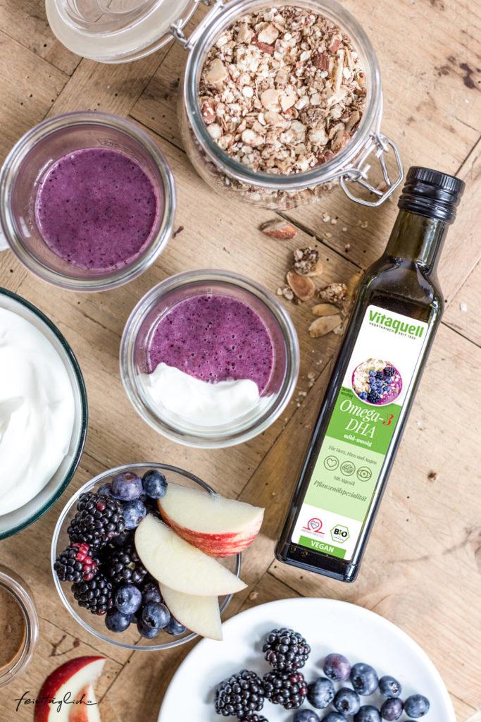Geschichtetes Frühstücksglas mit Blaubeer-Smoothie-Bowl, selbst gemachtem Mandel-Zimt-Granola, frischen Brombeeren, Äpfeln und Joghurt, ein herbstliches Frühstücksrezept, Omega-3-DHA-Öl, Vitaquell