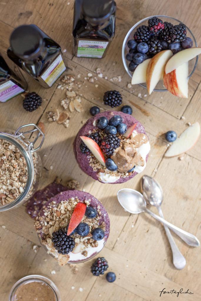 Geschichtetes Frühstücksglas mit Blaubeer-Smoothie-Bowl, selbst gemachtem Mandel-Zimt-Granola, frischen Brombeeren, Äpfeln und Joghurt, ein herbstliches Frühstücksrezept
